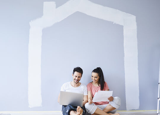 Couple sitting in new apartment using laptop
